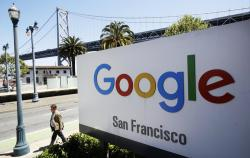 In this May 1, 2019, file photo a man walks past a Google sign outside with a span of the Bay Bridge at rear in San Francisco