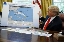 President Donald Trump holds a chart as he talks with reporters after receiving a briefing on Hurricane Dorian in the Oval Office of the White House.