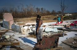 A woman is overcome as she looks at her house destroyed by Hurricane Dorian, in High Rock, Grand Bahama, Bahamas.