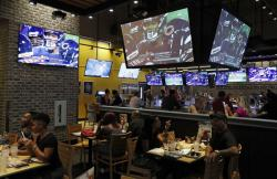 People eat and watch football at a Buffalo Wild Wings, Thursday, Sept. 5, 2019, in Las Vegas. MGM Resorts International and Buffalo Wild Wings are launching a mobile football game app for customers to pick favorite NFL teams, choose weekly fantasy performers and make proposition picks