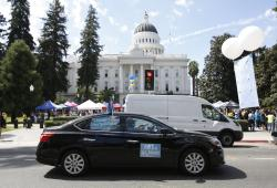 Dozens of supporters of a measure to limit when companies can label workers as independent contractors circle the Capitol during a rally in Sacramento, Calif., Wednesday, Aug. 28, 2019