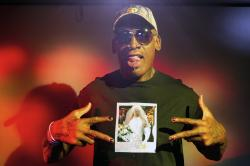Former NBA star Dennis Rodman poses wearing a T-shirt depicting himself in a wedding dress at a 1996 book promo event, in Los Angeles.