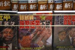 In this July 4, 2019, file photo, magazines with a front cover featuring Chinese President Xi Jinping and U.S. President Donald Trump on trade war is placed on sale at a roadside bookstand in Hong Kong