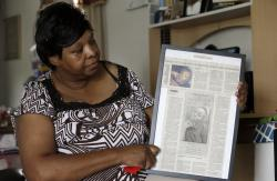Brenda Scurlock is shown in her home in Lumber Bridge, N.C. holding a newspaper clipping about her son's murder.