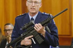 In this April 2, 2019, file photo, police acting superintendent Mike McIlraith shows New Zealand lawmakers in Wellington, an AR-15 style rifle similar to one of the weapons a gunman used to slaughter 51 people at two Christchurch mosques