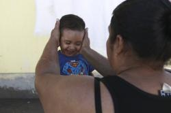 A migrant mother washes her son's face at the Pan de Vida shelter where they are living in Ciudad Juarez, Mexico, while waiting for a chance to request asylum in the United States, Thursday, Sept. 12, 2019