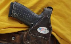 In this April 14, 2018 file photo, a man wears an unloaded pistol during a pro gun-rights rally in Austin, Texas