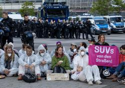 Activists block the main entrance of the fairground in Frankfurt, Germany, Sunday, Sept. 15, 2019. They protest against the government's transport policy on occasion of the IIA Auto Show taking place. The poster reads: 'SUV's out of the streets'.