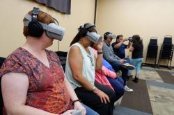 In this Sept. 6, 2019, photo provided by Ways of Knowing, audience members try out virtual reality headsets to watch a film titled 'Ways of Knowing,' which was directed by artist Kayla Briet, at the El Morro Events Center in Gallup, N.M.