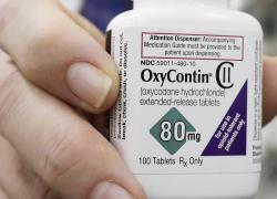 In this April 2, 2018, file photo, a pharmacist in San Francisco poses for photos holding a bottle of OxyContin