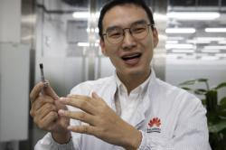 In this Aug. 21, 2019, photo, a Huawei research engineer holds up a coated screw designed to reduce signal interference at the Huawei Materials lab in Dongguan in Southern China's Guangdong province