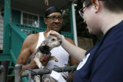 In this Tuesday, Aug. 27, 2019 photo, Sylvanus Jackson brings his dog out to meet Lizzy Trawick, a coordinator for LifeLine Animal Project's Pets for Life program in Atlanta