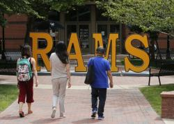 In this June 20, 2019, file photo students walk around a RAMS sign at Virginia Commonwealth University in Richmond, Va.