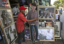 A vendor shows a cutout of Indonesian President Joko Widodo at his stall that sells portraits of Indonesian leaders, in Jakarta, Indonesia.
