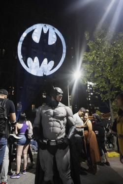 A man dressed in a Batman costume poses for a photo in front of the Batman signal projected on the Domino Sugar Refinery in honor of Batman Day in the Brooklyn borough of New York on Saturday, Sept. 21, 2019.