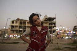 In this Thursday, Sept. 5, 2019, photo, Marwa, 10, poses for a portrait in a park near battle-ravaged buildings in Raqqa, Syria