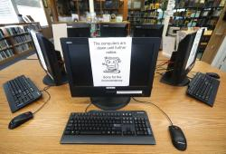 In this Aug. 22, 2019, file photo, signs on a bank of computers tell visitors that the machines are not working at the public library in Wilmer, Texas