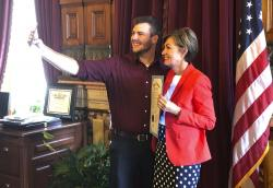 Carson King, of Altoona, Iowa, snaps a selfie Wednesday, Sept. 25, 2019, in the Iowa State Capitol in Des Moines, Iowa, with Iowa Gov. Kim Reynolds, who holds a proclamation declaring Saturday as Carson King Day