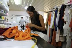 In this Wednesday, Sept. 4, 2019 photo designer Lydia Vousvouni of fashion firm Zeus+Dione works at the firms' atelier in Athens. Greece's financial crisis nearly snuffed out the country's centuries-old silk manufacturing tradition.