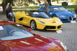 People looking at a Aston Martin One-77 Coupe (2011) in front of a Ferrari LaFerrari (2015), yellow, and a Bugatti Veyron EB 16.4 Coupe (2010), blue, part of some 25 luxury cars owned by Teodoro Obiang, the son of the Equatorial Guinea's President Teodoro Obiang Nguema Mbasogo are pictured before an auction of sales house Bonhams at the Bonmont Abbey Golf & Country Club in Cheserex near Geneva, Switzerland, Sunday, Sept. 29, 2019