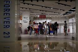 Women select clothing at an American fast fashion retailer Forever 21.