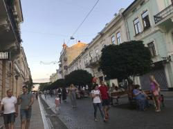 Families and friends strolling down the cobblestoned Kobilyanska pedestrian street in Chernivtsi, Ukraine.
