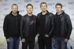 Members of Nickelback pose for photographers as they arrive on the red carpet at the Juno Awards in Ottawa.
