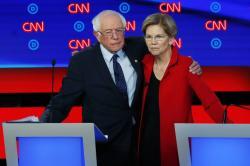 Sen. Bernie Sanders, I-Vt., and Sen. Elizabeth Warren, D-Mass., embrace after the first of two Democratic presidential primary debates.