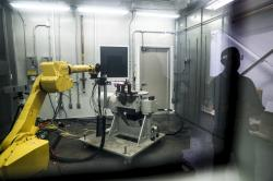 In this May 18, 2017, file photo, a robotic arm with a high-intensity blowtorch is remotely operated to test ceramic matrix composites, which make engines more durable, heat-resistant and efficient, at the General Electric Aviation plant in Evendale, Ohio