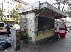 A man removes stickers from a kebab grill in Berlin, Germany.