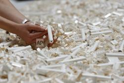 In this Friday July 26, 2019, file photo, a visitor looks through Lego pieces provided for a project at the Tate Modern, in London