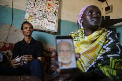 Gerald Erebon sits with his aunt, Scolastica Apayo, as she holds a phone displaying a photo of the Rev. Mario Lacchin, during an interview at her home in the Isiolo area of the Archers Post settlement in Kenya on Sunday, June 30, 2019