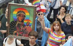 People take part in a gay pride parade holding up an image of Madonna and Baby Jesus that has offended many Catholics in Plock, Poland.