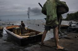 Fishermen covered in oil get their boat ready for fishing on Lake Maracaibo near La Salina crude oil shipping terminal in Cabimas, Venezuela, July 9, 2019