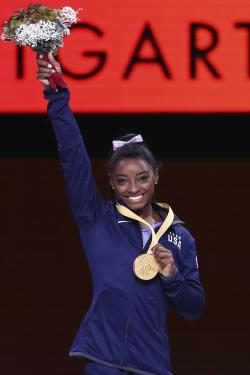 Gold medalist Simone Biles of the United States celebrates during the award ceremony for the balance beam in the women's apparatus finals at the Gymnastics World Championships in Stuttgart, Germany, Sunday, Oct. 13, 2019. (AP Photo/Matthias Schrader)