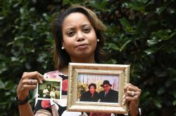 In this Sept. 6, 2019, photo, Donna Cryer holds up family photos that include her father Roland Henry, as she poses for a photo in Washington