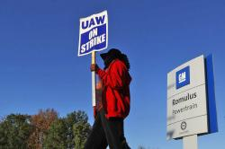 In this Oct. 9, 2019, file photo, Yolanda Jacobs, a United Auto Workers member, walks the picket line at the General Motors Romulus Powertrain plant in Romulus, Mich.