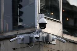 In this photo taken Sept. 25, 2019, high-tech video cameras hang from an office building in downtown Belgrade, Serbia