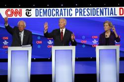 Democratic presidential candidate Sen. Bernie Sanders, I-Vt., left, former Vice President Joe Biden, center, and Sen. Elizabeth Warren, D-Mass., raise their hands to speak during a Democratic presidential primary debate.
