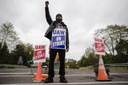 Ryan Piper with the United Auto Workers continues to picket after news of a tentative contract agreement with General Motors, in Langhorne, Pa., Wednesday, Oct. 16, 2019