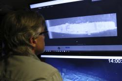 In this Wednesday, Oct. 16, 2019, photo, Vulcan Inc. director of subsea operations on the Petrel, Rob Kraft, left, looks at images of the Japanese aircraft carrier Kaga, off Midway Atoll in the Northwestern Hawaiian Islands
