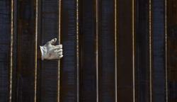 A construction worker's gloved hand is seen through a portion of the 30-foot tall bollard fence as work continues on the U.S./Mexico border fence two miles east of the Lukeville, Arizona port of entry on Oct. 8, 2019