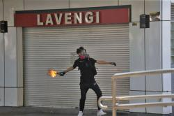 A protester throws a Molotov cocktail at a police station in Hong Kong, Sunday, Oct. 20, 2019
