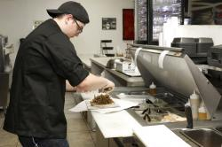 Chef Joseph Gattuso prepares a gyro sandwich. He's working in the kitchen of Frato's Pizza, but filling an online order for the virtual restaurant Halal Kitchen.