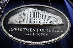 In this Thursday, April 18, 2019, file photo, a sign for the Department of Justice hangs in the press briefing room at the Justice Department, in Washington