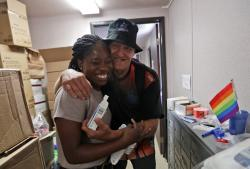 Photo IDEA Exchange social worker Elisha Ekowo, left, is hugged by Michael Ferraro, as he picks up his HIV medication, in Miami.