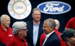In this Monday, July 15, 2019, file photo, United Auto Workers Local 600 President Bernie Ricke, left, talks with Ford Motor Co., President Automotive Joseph R. Hinrichs after opening contract talks in Dearborn, Mich.