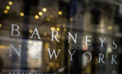 Signage for Barneys New York department store is displayed on the store's window in New York.
