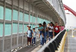 Local residents with visas walk across the Puerta Mexico international bridge to enter the U.S.