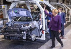 German Chancellor Angela Merkel waves to workers on the pro duction line for the production of the electric car ID.3 in Zwickau, eastern Germany, Monday, Nov.4, 2019